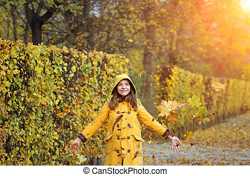 autumn leaves fall around teenage girl in the park