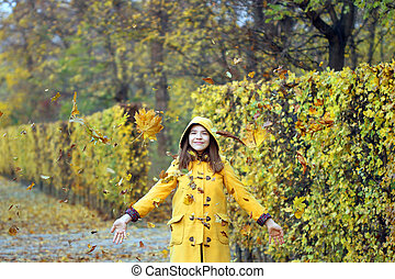 autumn leaves fall around the girl in the park