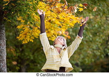 Autumn Leaves Falling On Happy Senior Woman - Autumn leaves...