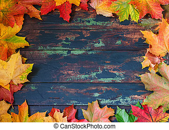 Autumn leaves frame, brown wooden background.
