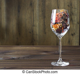 Autumn leaves in a wine glass on wooden table background