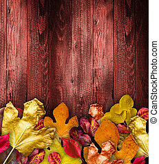 Autumn Leaves over a Natural Dark Wooden background. Old dirty wood tables or parquet with knots and holes and aged partculars.
