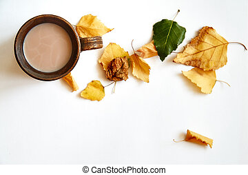 Autumn leaves with coffee or tea cup on white background. Flat lay. Copy space