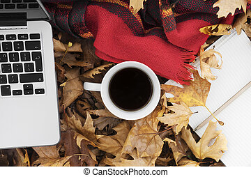 Autumn leaves with cup of coffee, laptop and notebook.