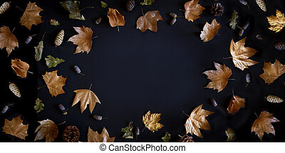 Autumn maple leaves frame on dark background with copyspace from above. November black friday sale and thanksgiving concept. Fall season natural flat lay border.