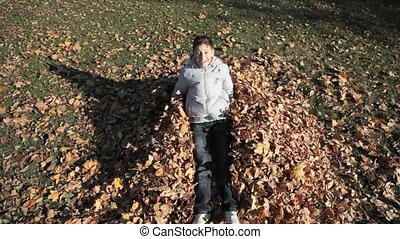 Autumn mess - Teen boy falling onto the hip of leaves and ...