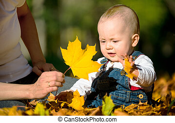 Autumn mood - baby playing with leaf