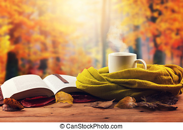 autumn mood - opened book, scarf and hot drink on the table