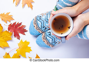autumn mood, yellow leaves, cup of hot tea in hands and warm wool socks on white background top view