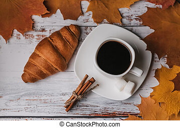 Autumn morning Breakfast with a Cup of coffee and a croissant on a wooden table with maple leaves