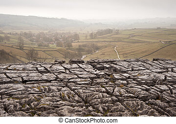Autumn morning over liomestone pavement at Malham Cove looking along Malham Dale in Yorkshire Dales National Park
