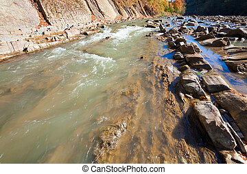 Autumn mountain stony river view with some rapids and stony edges