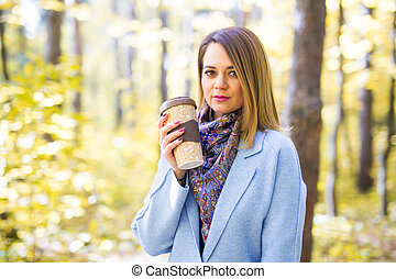 Autumn, nature and people concept - Young beautiful woman in blue coat holding a cup of coffee