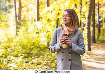 Autumn, nature and people concept - Young beautiful woman in grey coat holding a cup of coffee