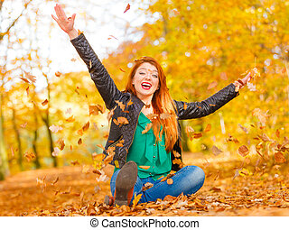 Cheerful girl is sitting in park.