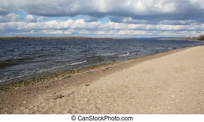 autumn nature scene, sandy bank of river, sky with clouds