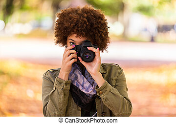 Autumn outdoor portrait of beautiful African American young woman holding a digital camera - Black people