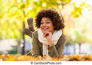 Autumn outdoor portrait of beautiful African American young woman lying down - Black people