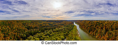 Autumn panoramic aerial view over the Isar river in southern bavaria, framed by wonderful colored trees at a beautiful evening, the sun in shining.