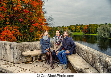 Autumn Park. Two girls and one guy talking, sitting on a stone bench.