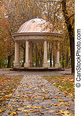 Autumn park with a footpath to summer house