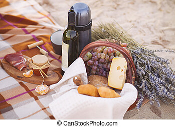 Autumn picnic by the sea with wine, grapes, bread and cheese