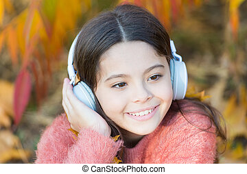 Autumn playlist concept. Enjoy music outdoors fall warm day. Audio file. Educational podcast. Feel joy. Kid girl relaxing near autumn tree with headphones. Music for autumn cozy mood. Listening song