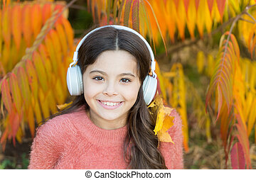 Autumn playlist concept. Feel joy. Kid girl relaxing near autumn tree with headphones. Music for autumn cozy mood. Listening song. Enjoy music outdoors fall warm day. Audio file. Educational podcast