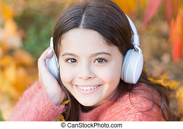 Autumn playlist concept. Music for autumn cozy mood. Listening song. Enjoy music outdoors fall warm day. Audio file. Educational podcast. Feel joy. Kid girl relaxing near autumn tree with headphones