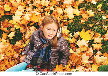 Autumn portrait of a cute little girl of 8 years old, playing with yellow leaves in the park, top view