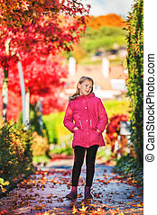Autumn portrait of a cute little girl wearing bright pink jacket and boots