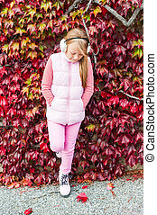 Autumn portrait of a cute little girl, wearing pink jacket without sleeves and white earmuffs
