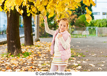Autumn portrait of adorable little girl, wearing pink waistcoat and warm knitted skirt