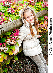 Autumn portrait of adorable little girl wearing warm beige coat
