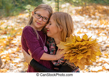 Autumn portrait of cuddling mother and daughter