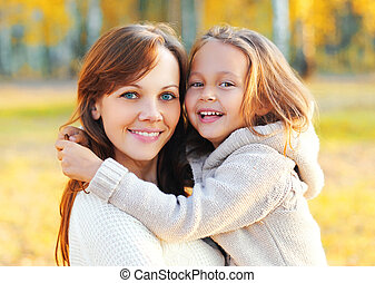 Autumn portrait of happy smiling mother with her daughter child in the park