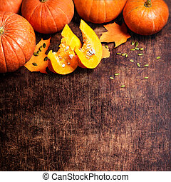 Autumn Pumpkin Background - orange pumpkins over wooden table. Thanksgiving, Halloween, Fall concept. Greeting card with copy space for text