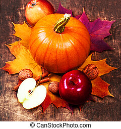 Autumn Pumpkin Thanksgiving Background with orange pumpkins, apples and fallen leaves on wooden table