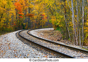 Railroad track curve around the bend and out of sight through trees with beautiful fall foliage. Shot in rural central Indiana.