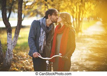 Autumn romance - Young couple kissing in autumn park