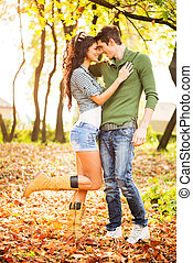 Autumn Romance - Young heterosexual couple in love in park,...