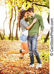 Autumn Romance - Young heterosexual couple in love in park,...