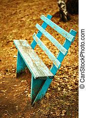 Autumn sadness concept. Empty blue bench.