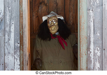 Autumn Scarecrow peeking out from a outhouse.