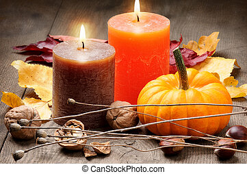 Autumn setting with candles, pumpkin, walnuts and leaves
