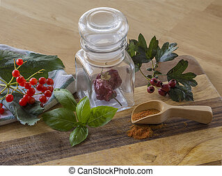 autumn spices still life chili pepper in glass spice jar wooden scoop basil leaves rowan berry and on wooden cutting board
