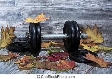 Dumbbell with leaves on a wooden background.