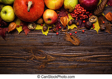 autumn still life, harvested pumpkins with fall leaves and autumn fruit, gifts of autumn, copy space, wooden background, walnuts, maple leaves - autumn composition from top. Free space for text