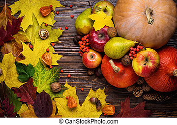 autumn still life, harvested pumpkins with fall leaves and autumn fruit, gifts of autumn, wooden background, walnuts, maple leaves - autumn composition from top.