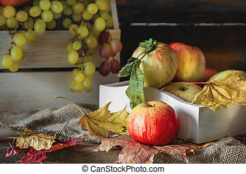Autumn still life of apples and leaves in a box with green grapes.